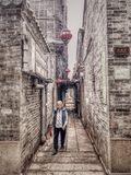 An Old Woman Walking In The Alley Stock Image