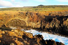 Ana Kai Tangata Cave. Waves breaking at the cliffs in front of the Ana Kai Tangata Cave close to Hanga Roa in Rapa Nui, Easter Island in Chile, South America royalty free stock image