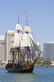 Anachronism. An old-fashioned sailing ship sails past a modern city Stock Photography