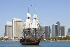 Anachronistic. An old-fashioned sailing ship sails past a modern city Stock Photo