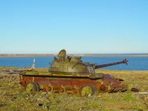 Debris of ancient Soviet battle tank corroding outdoors on scrap metal storehouse on scenic natural landscape background. Symbol o stock photography