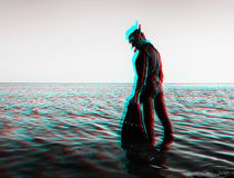 Anaglyph effect of man in a diving suit with flippers. Young man wearing in a diving suit with a mask and flippers standing in the sea over water surface. Image stock image