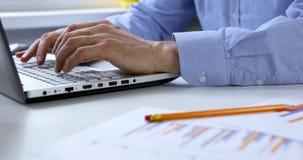 Analítica do negócio - homem que trabalha com relatórios financeiros no escritório no laptop vídeos de arquivo