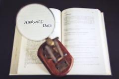 Analice la lupa de los datos en la investigación de la lectura del libro imágenes de archivo libres de regalías