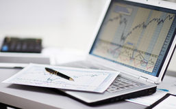 Analisando cartas do investimento com portátil Foto de Stock Royalty Free