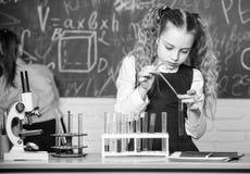 Analisi chimica Liquidi chimici di studio dell'allievo della scuola Lezione di chimica della scuola Provette con le sostanze Labo fotografia stock