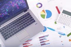 Analisi dei dati - posto di lavoro con i grafici e grafici commerciali, computer portatile e calcolatore immagini stock