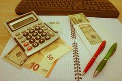 Analisi del bilancio annuale con il calcolatore ed i soldi sulla tavola Penna, occhiali e grafici immagini stock