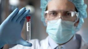 Analisi del sangue esperta della tenuta del laboratorio per gli anticorpi di HIV, prevenzione di infezione fotografia stock libera da diritti