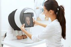 Analisi della pelle del fronte Donna a cosmetologia che fa sistema diagnostico della pelle fotografie stock