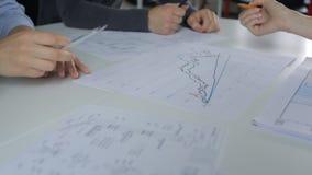 Analisi e discussione sui grafici sulla tavola, sul maschio e sulla mano femminile con una matita stock footage
