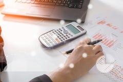 Analista de mercado joven de finanzas que trabaja en la oficina soleada en el ordenador portátil mientras que se sienta en la tab foto de archivo