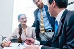Analista di affari che sorride mentre interpretando i rapporti finanziari SH immagini stock