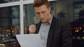 Analista do negócio do homem novo que usa a lupa a verificar o contrato no escritório vídeos de arquivo