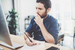 Analista elegante novo da finança da operação bancária que trabalha no escritório ensolarado no portátil ao sentar-se na tabela d imagem de stock