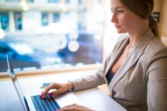 Analista especializado fêmea dos imóveis comerciais para incorporar a informação ao netbook fotografia de stock royalty free