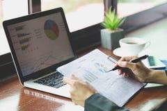 Analista financeiro com original em suas mãos que lê a informação no tela de computador foto de stock