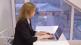Analista financiero de la mujer de negocios que trabaja con el gráfico y la carta en el ordenador portátil almacen de video