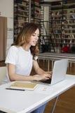 Analista lungo dei capelli della giovane donna astuta che lavora all'ufficio dilavoro sul computer portatile, scaffale per libri  fotografia stock libera da diritti
