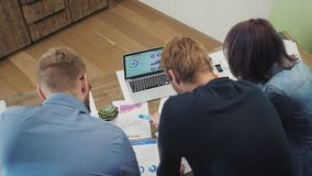 Analistas en el trabajo de escritorio en el ordenador portátil que muestra estadísticas, mirando gráficos y cartas metrajes
