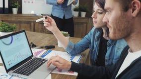 Analisti su un computer portatile che mostra le statistiche, esaminando i grafici ed i grafici video d archivio