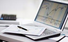 Analizar cartas de la inversión con el ordenador portátil Foto de archivo libre de regalías