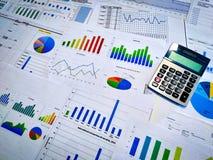 analizar cartas y gráficos de la renta con la calculadora Cierre para arriba Análisis financiero del negocio y concepto de la est fotografía de archivo