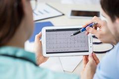 Analizar el electrocardiograma en una tableta Foto de archivo libre de regalías
