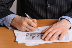 Analizing business chart. Businessman with pen analysing the financial bar chart Royalty Free Stock Images