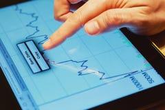 Analizzare i dati finanziari su uno schermo della compressa fotografia stock