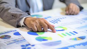 analizzare i grafici ed i grafici di reddito con il calcolatore fotografie stock