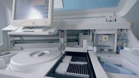 Analizzatore biochimico moderno riempito di provette video d archivio
