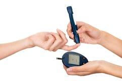 Analizzatore del tester del glucosio della tenuta del braccio di medici sui pazienti dito e sul monitor di misura in altra mano fotografie stock libere da diritti