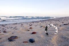 Analog aged clock face on sea beach sand Stock Photo
