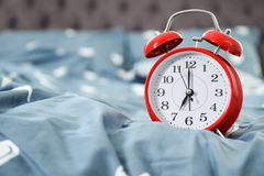 Analog alarm clock on bed. Time of day royalty free stock image
