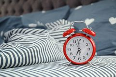 Analog alarm clock on bed. Time of day royalty free stock photo