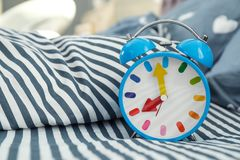 Analog alarm clock on bed. Time of day stock images