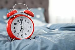 Analog alarm clock on bed. Time of day stock photo