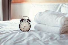 Analog Alarm Clock on Bedroom in Modern House, Retro Timer at 7.00 a.m. on White Cover Bed.  royalty free stock images