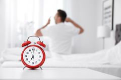 Analog alarm clock and blurred man. On background. Time of day royalty free stock photos