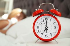 Analog alarm clock and blurred sleepy woman. On background. Time of day royalty free stock image