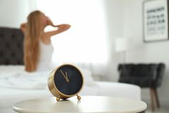 Analog alarm clock and blurred woman. On background. Time of day royalty free stock image