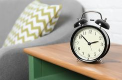 Analog alarm clock on side table in living room, space for text. Time of day royalty free stock images