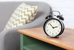 Analog alarm clock on side table in living room. Space for text. Time of day stock image