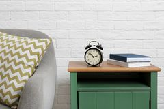 Analog alarm clock on side table in living room. Time of day stock photos