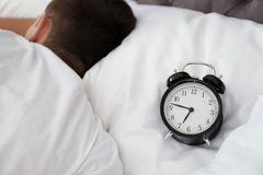 Analog alarm clock and sleepy man in bed. Time of day royalty free stock photos