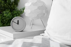 Analog alarm clock on table in bedroom. Time of day stock photos