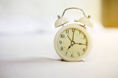 Analog alarm clock on white bed, time in the mornign with a brig. Ht sunshine Stock Photos