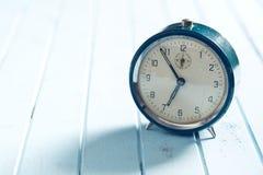 Analog alarm clock on wooden table Stock Photo