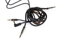 Analog audio cables with mini stereo connectors on white background. Two different analog audio cables with gold-plated stereo connectors mini jack on a white stock photography